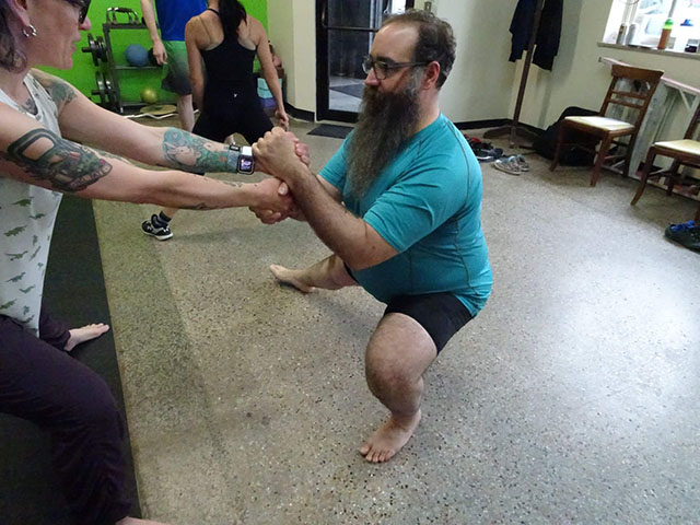 Beardy and I learning about partner assisted squats AND learning about taking time for us. Like Brussels sprouts with bacon, we loved it! Photo by Ray Shonk, 2018.