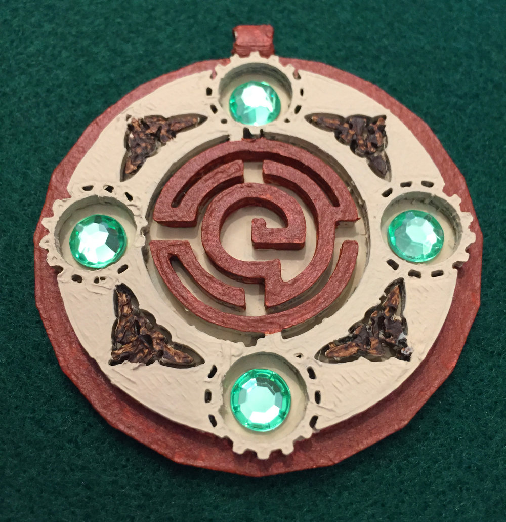 Wooden style pendant made partially of dragonbone with gemstones.