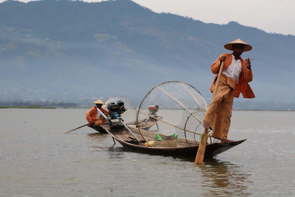 Pescador com sua maneira típica de remar com os pé.