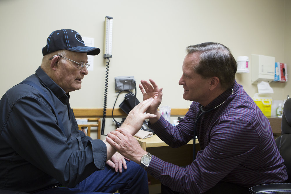 Dr. Dahl with a patient in his Magrath clinic.