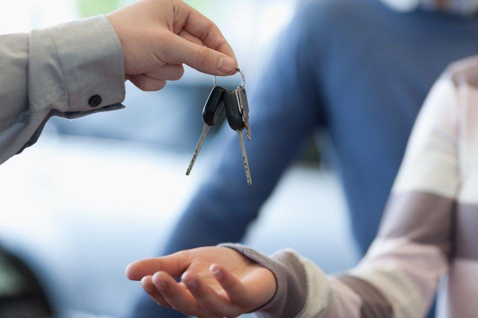 Car dealer giving keys to a customer in a car shop.jpeg