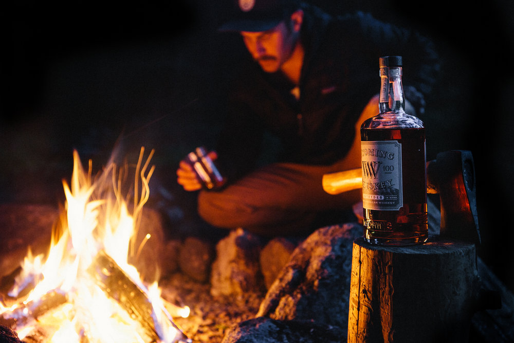 Wyoming Whiskey product photograph next to fire while camping - beverage photography - The Beans and Rice Commercial Outdoor Adventure & Lifestyle Content