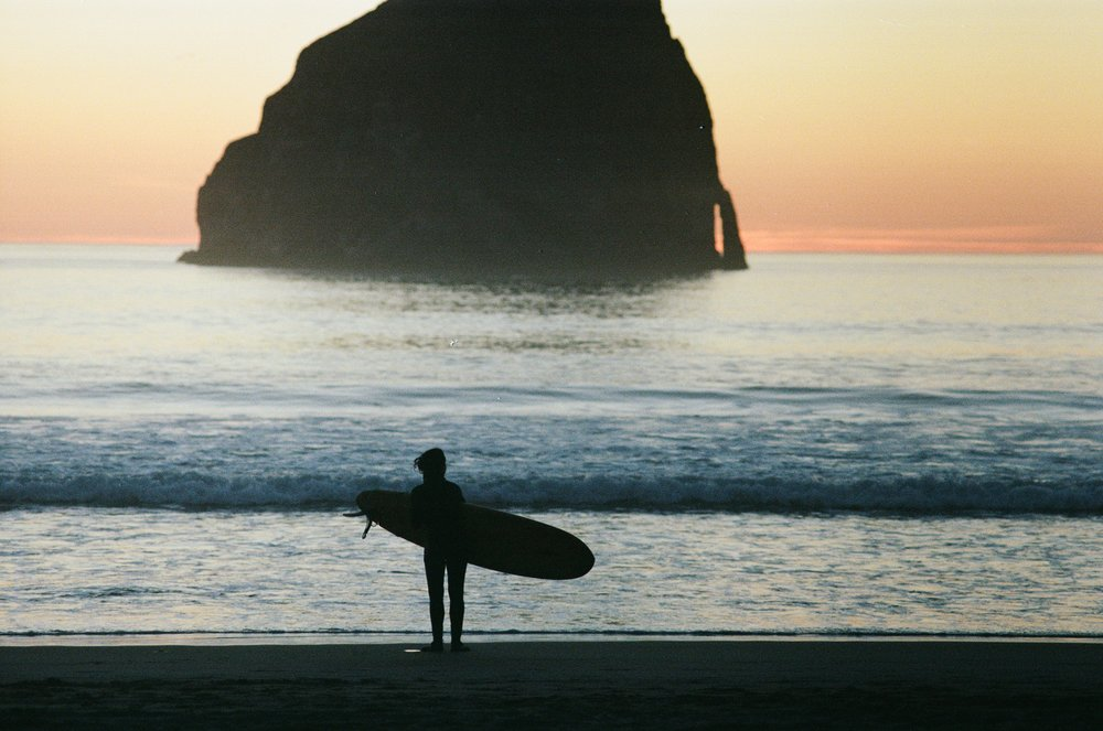 Lone surfer during standing on beach in Pacific City Oregon - Surf product photography - The Beans and Rice Commercial Outdoor Adventure & Lifestyle Content