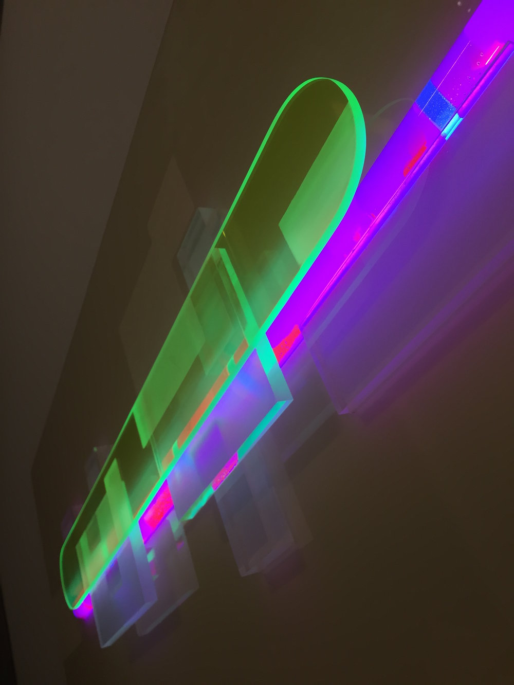 Light sculpture made of resin, acrylic, wood, and LED, with green, orange and purple colors entitled Beacon 4 Night.