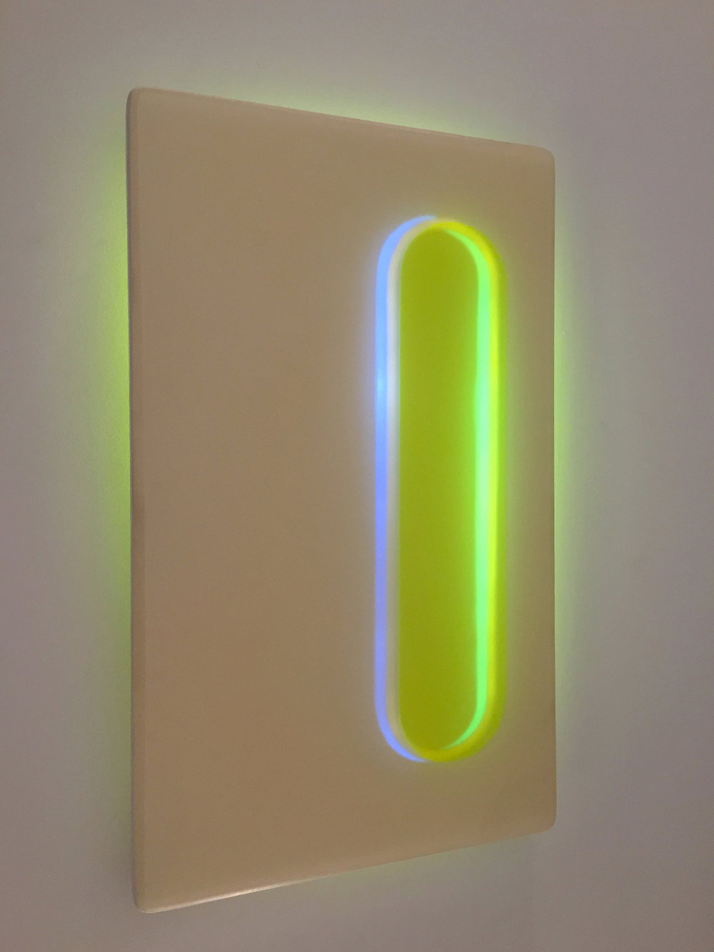 Light sculpture shown in daylight made of resin, acrylic, wood, and LED, with blue and green colors entitled Beacon 2 Night.