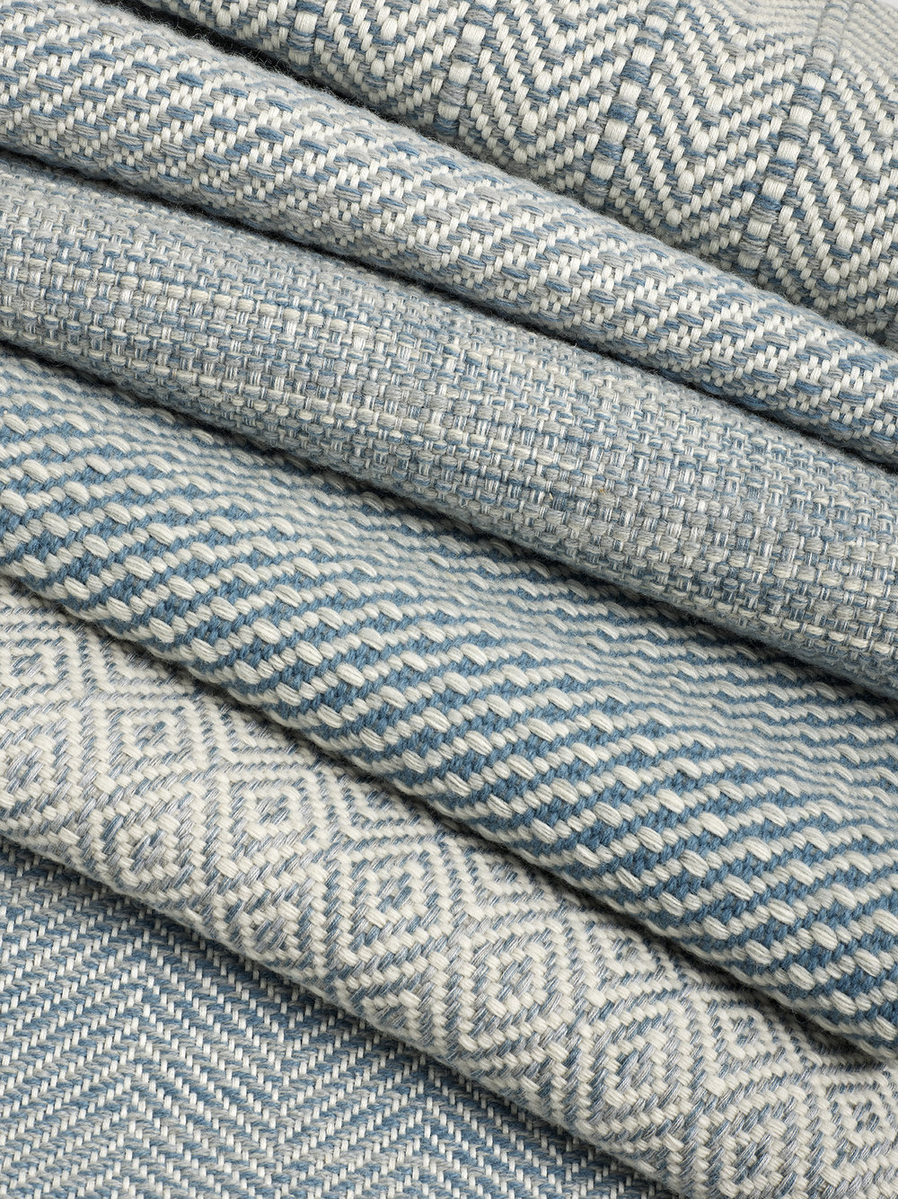 A stack of hand-woven rugs in neutral colors with different geometric patterns.