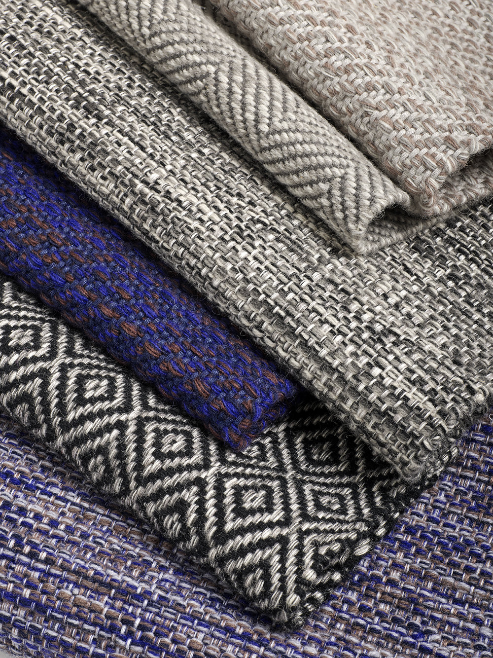 A stack of woven rugs in purple and gray with different geometric patterns.