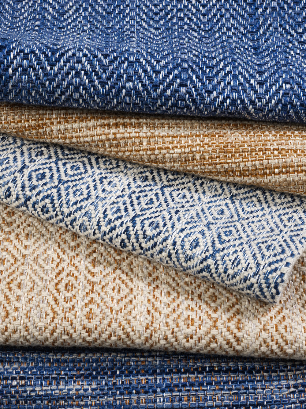 A stack of woven rugs in blue and orange with different geometric patterns.