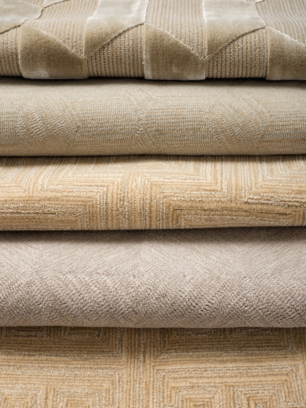 A stack of hand-tufted, silk wool rugs in neutral tones with different geometric patterns.