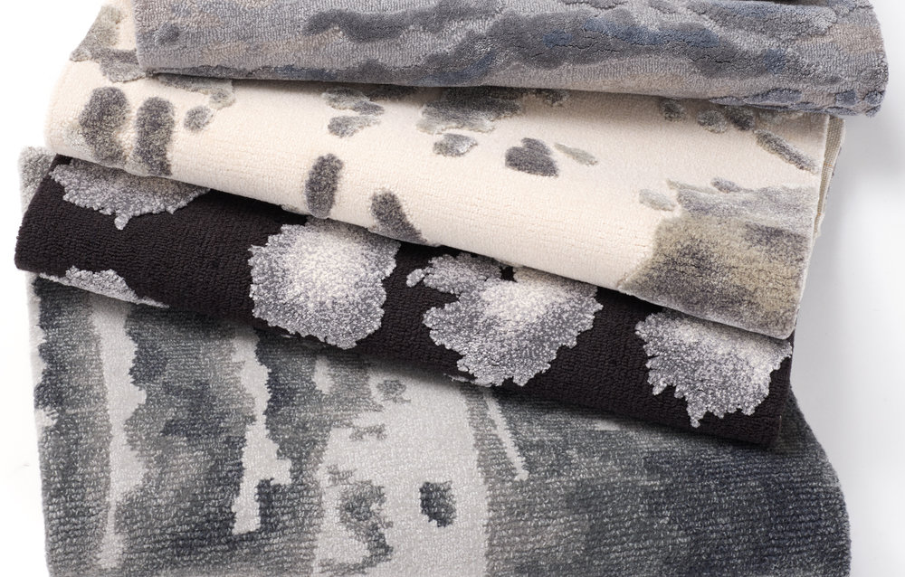 A stack of hand-tufted, silk wool rugs with custom abstract painterly designs in neutral grays and silvers.