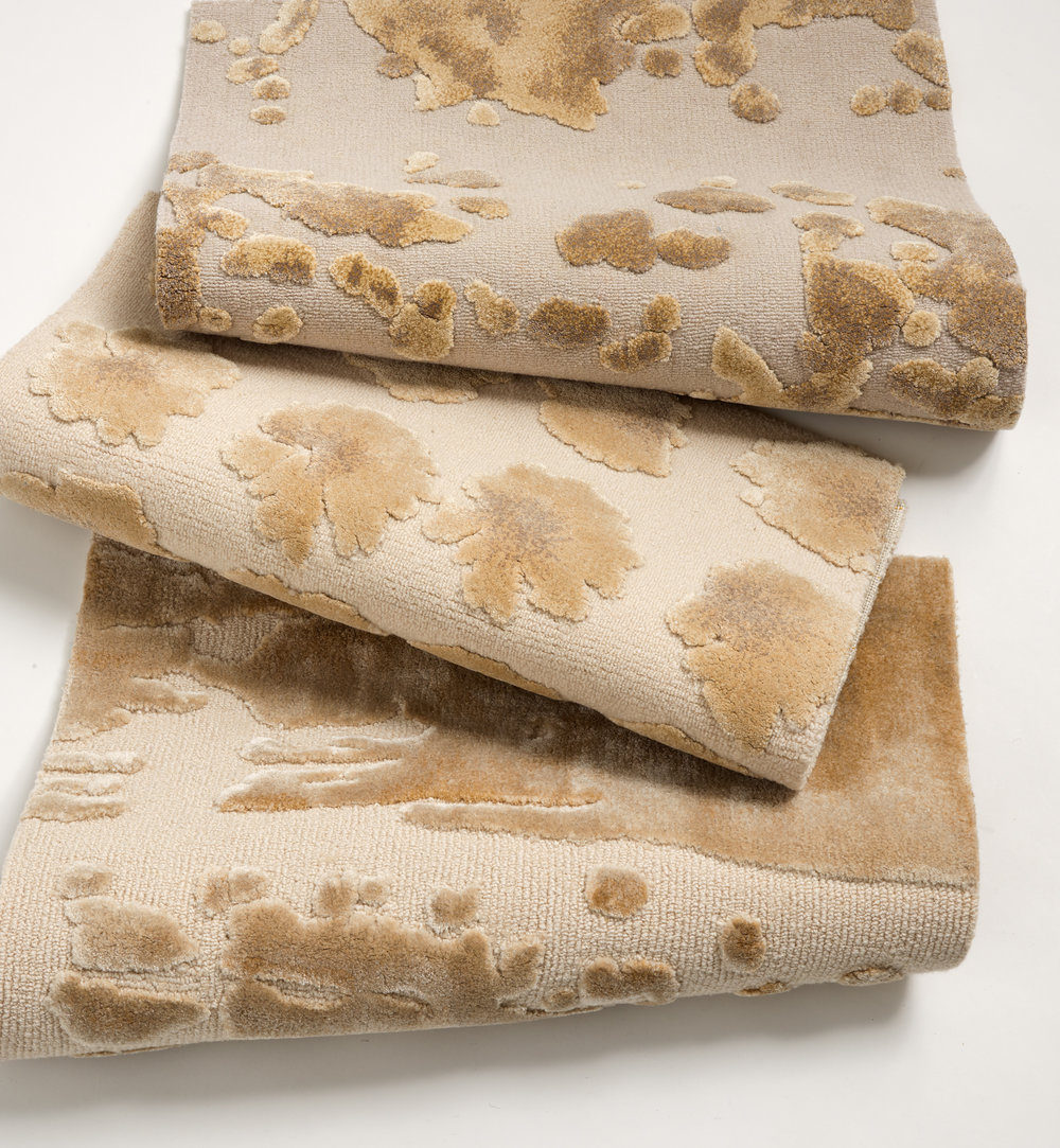 A stack of hand-tufted, silk wool rugs with custom abstract painterly designs in neutral cream and brown.