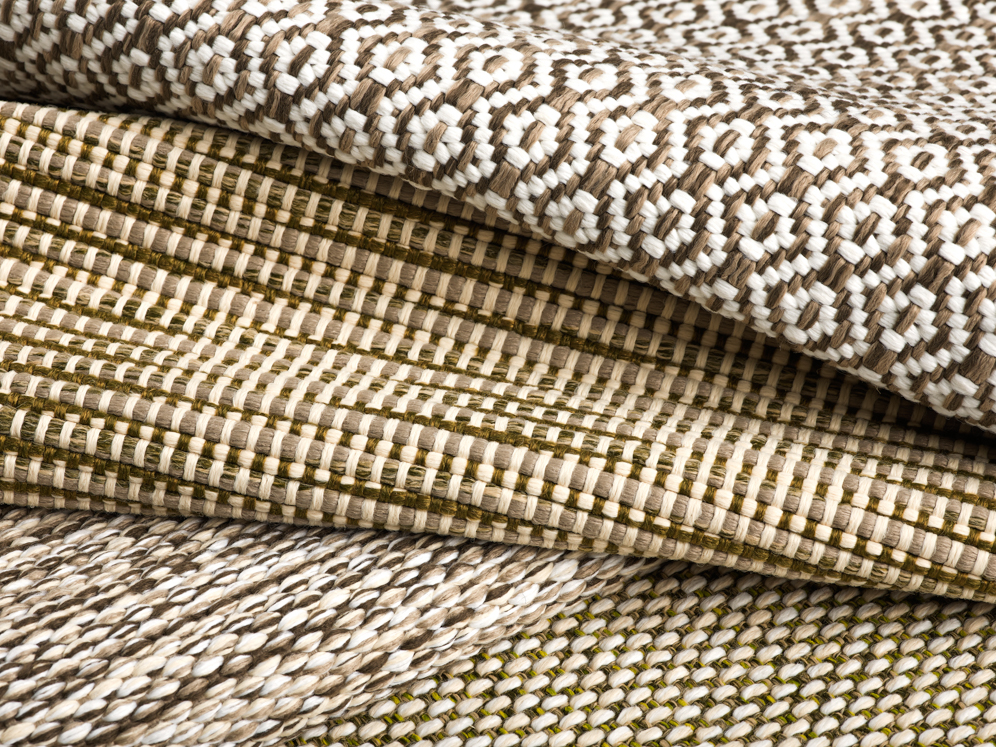 Stack of woven polypropylene outdoor rugs with geometric pattern in neutral colors.