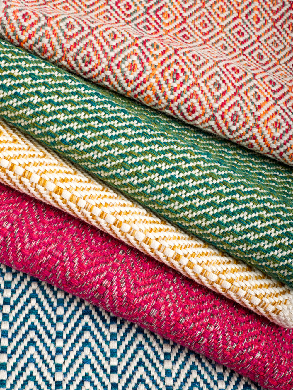 A stack of hand-woven rugs in jewel tones with different geometric patterns.