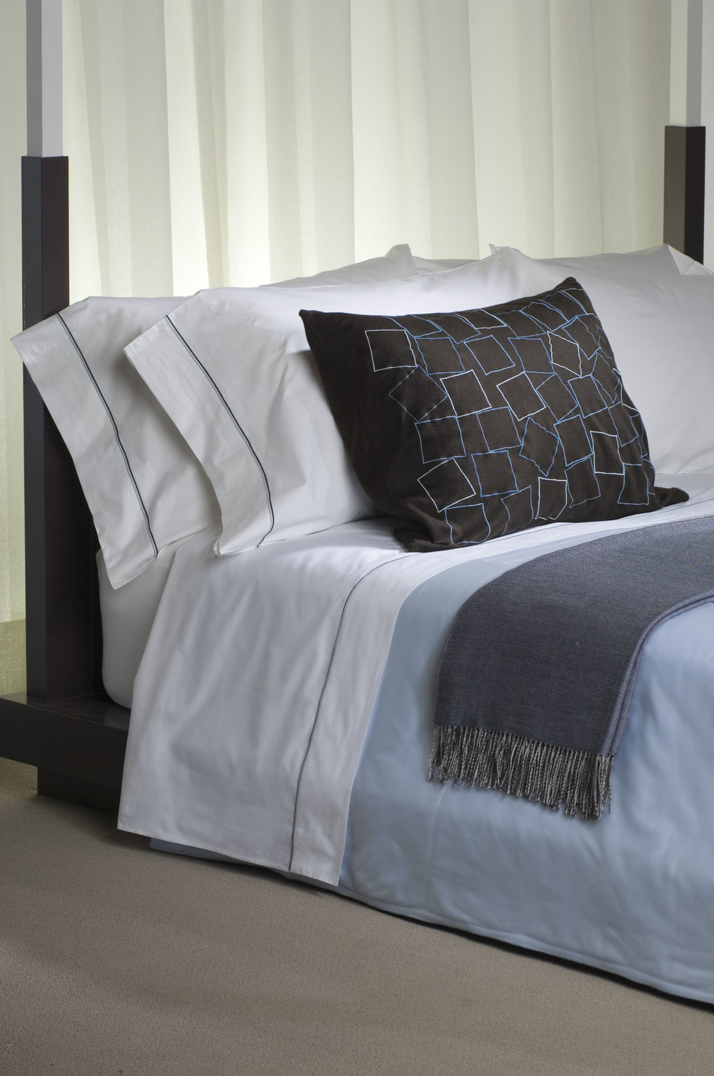 Modern designed home with sateen linens in black with blue embroidered details.