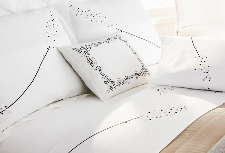 Modern designed home with sateen linens in white with black and gray embroidered details.