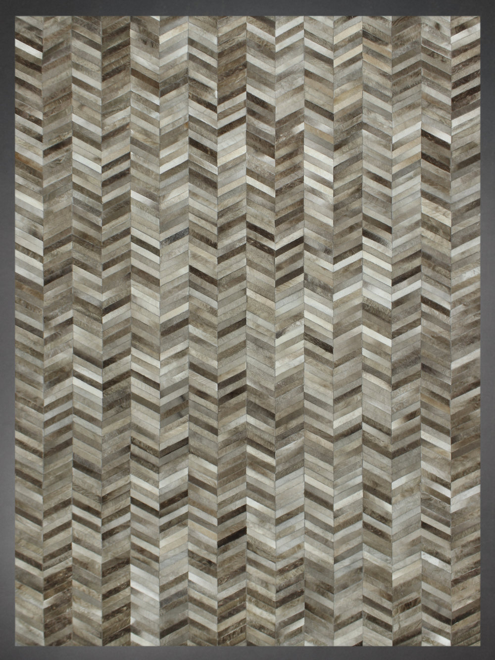 Contemporary designed fur rug in Herringbone style with grays, browns, and taupe.