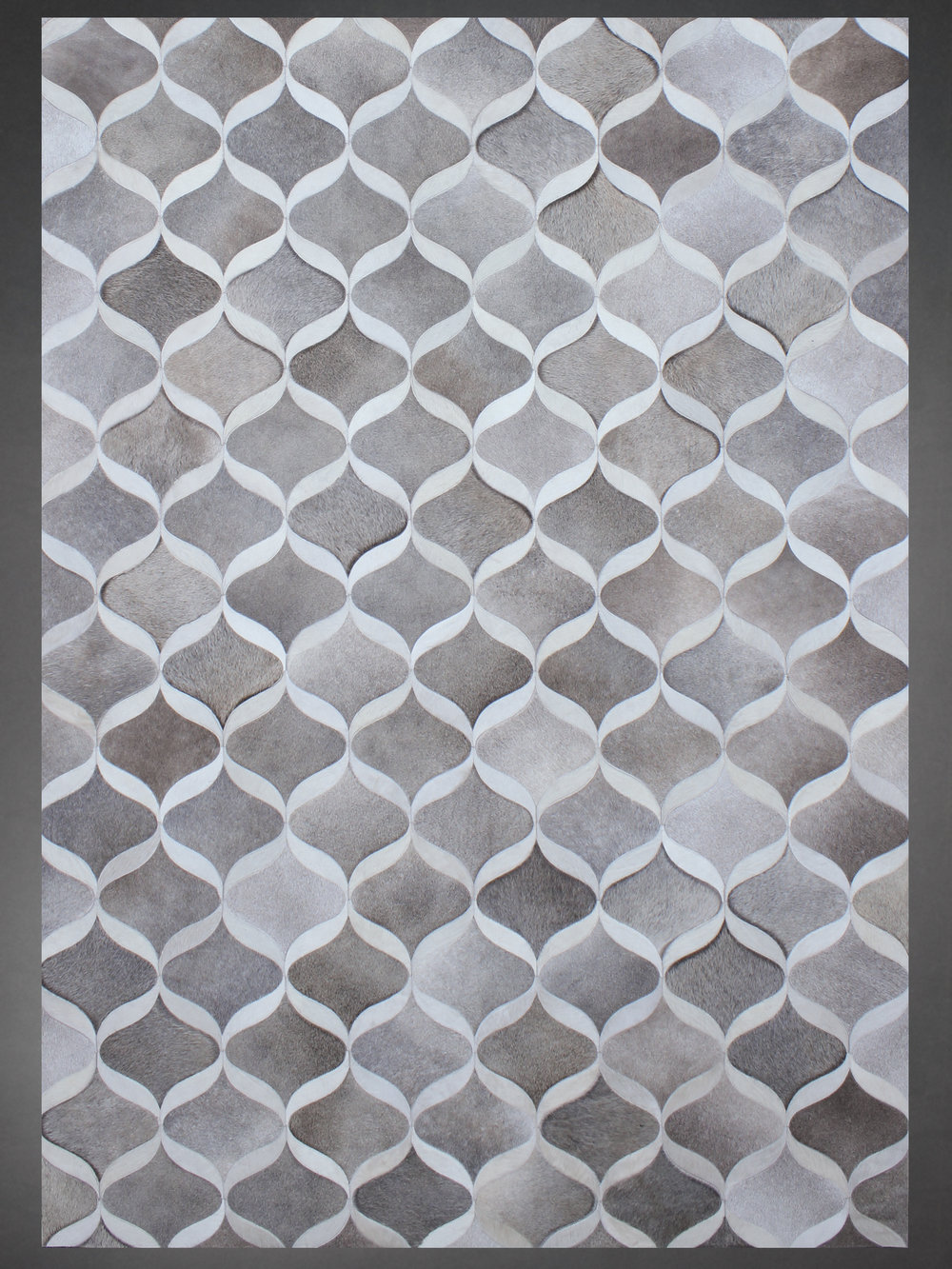 Contemporary designed fur rug in a geometric pattern in grays and browns.