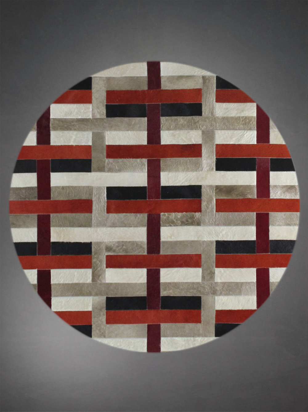 Contemporary designed fur circle rug in a geometric woven pattern in red and black.