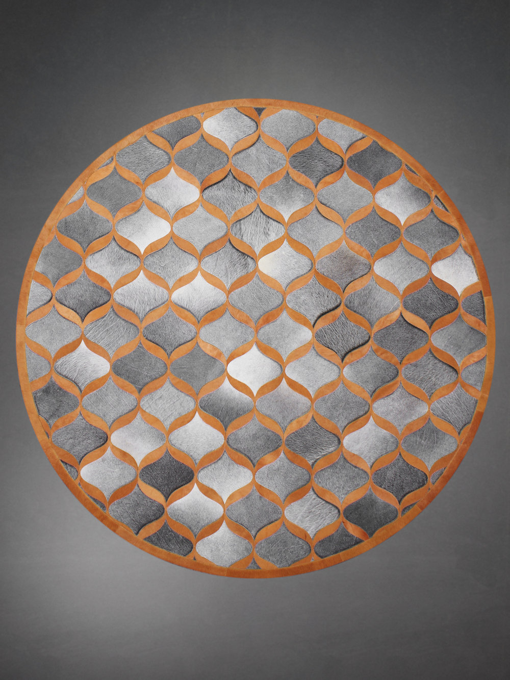 Contemporary designed fur circle rug in a geometric woven pattern in orange and gray.