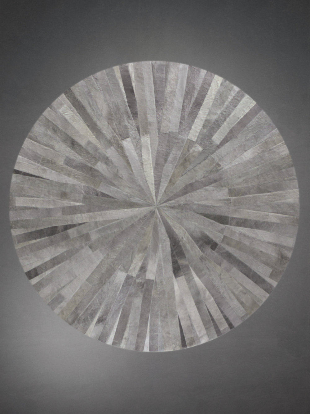 Contemporary designed fur circle rug in a geometric woven pattern in gray and silver.