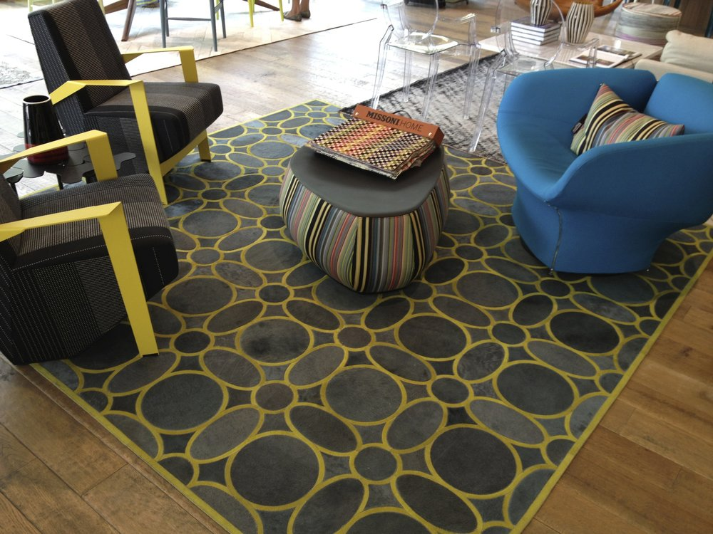 A contemporary, modern home with a fur rug in a geometric circle pattern in green.