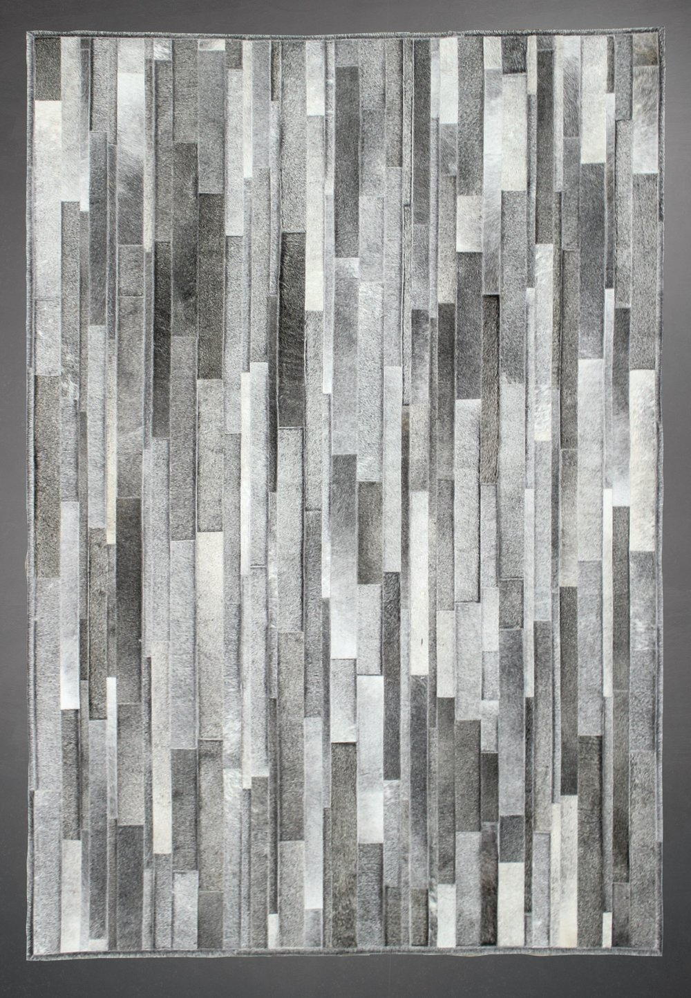 Contemporary designed fur rug in a striped pattern in grays and whites.