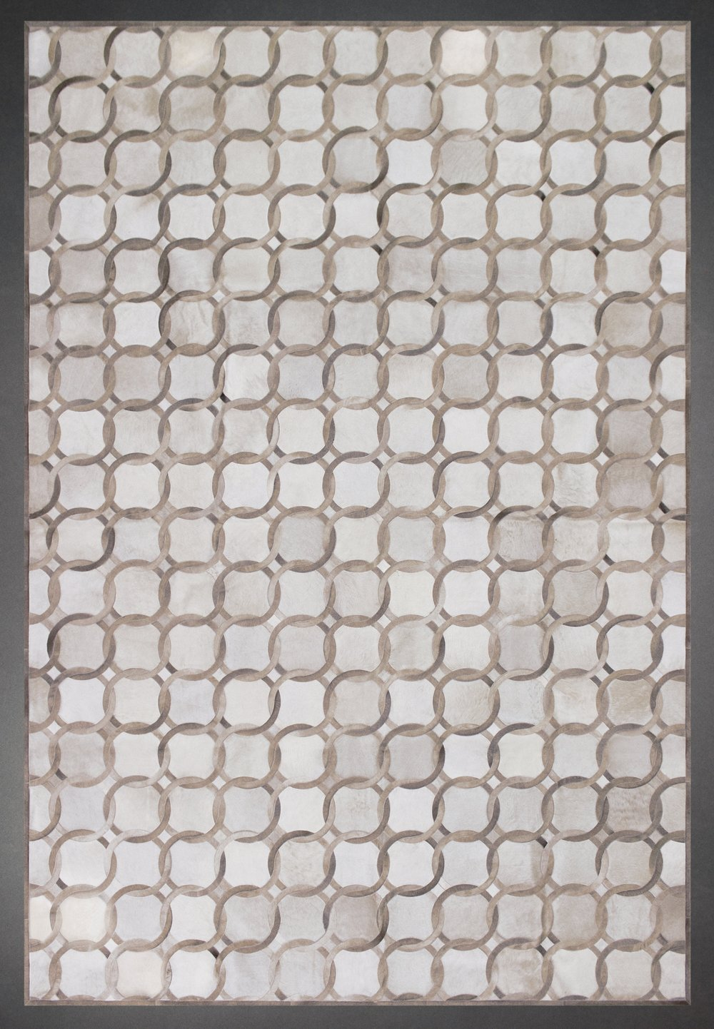 Contemporary designed fur rug in a square and circle pattern in grays and browns.