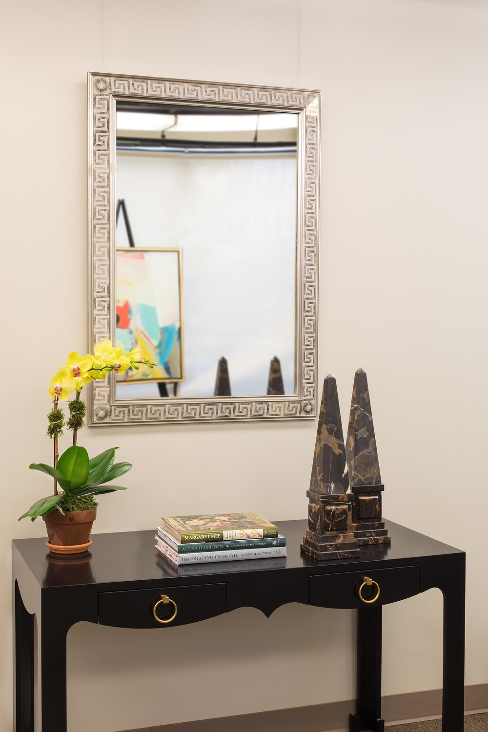 Silver framed mirror, hanging over wooden side table
