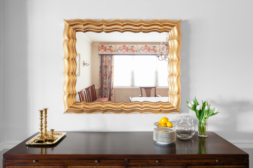 Rectangular gold framed mirror hanging on wall over wooden side table