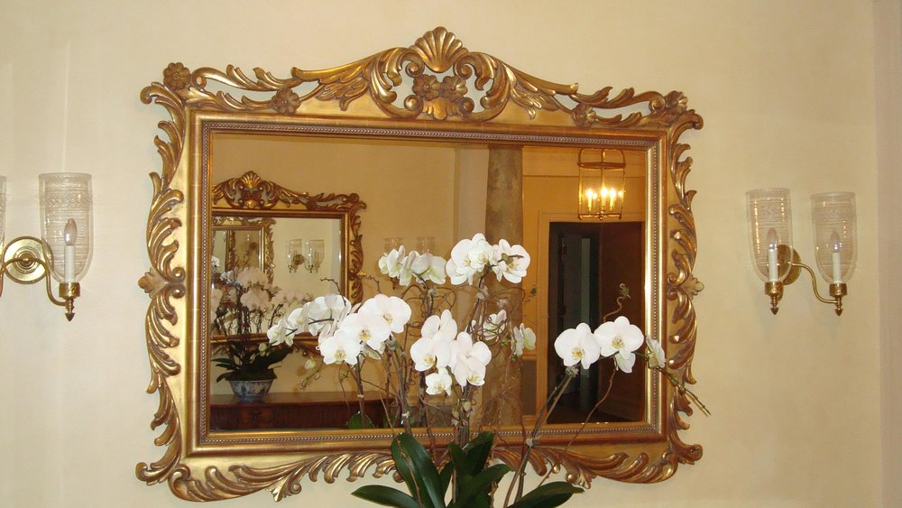 Gold guided decorative mirror hanging on wall