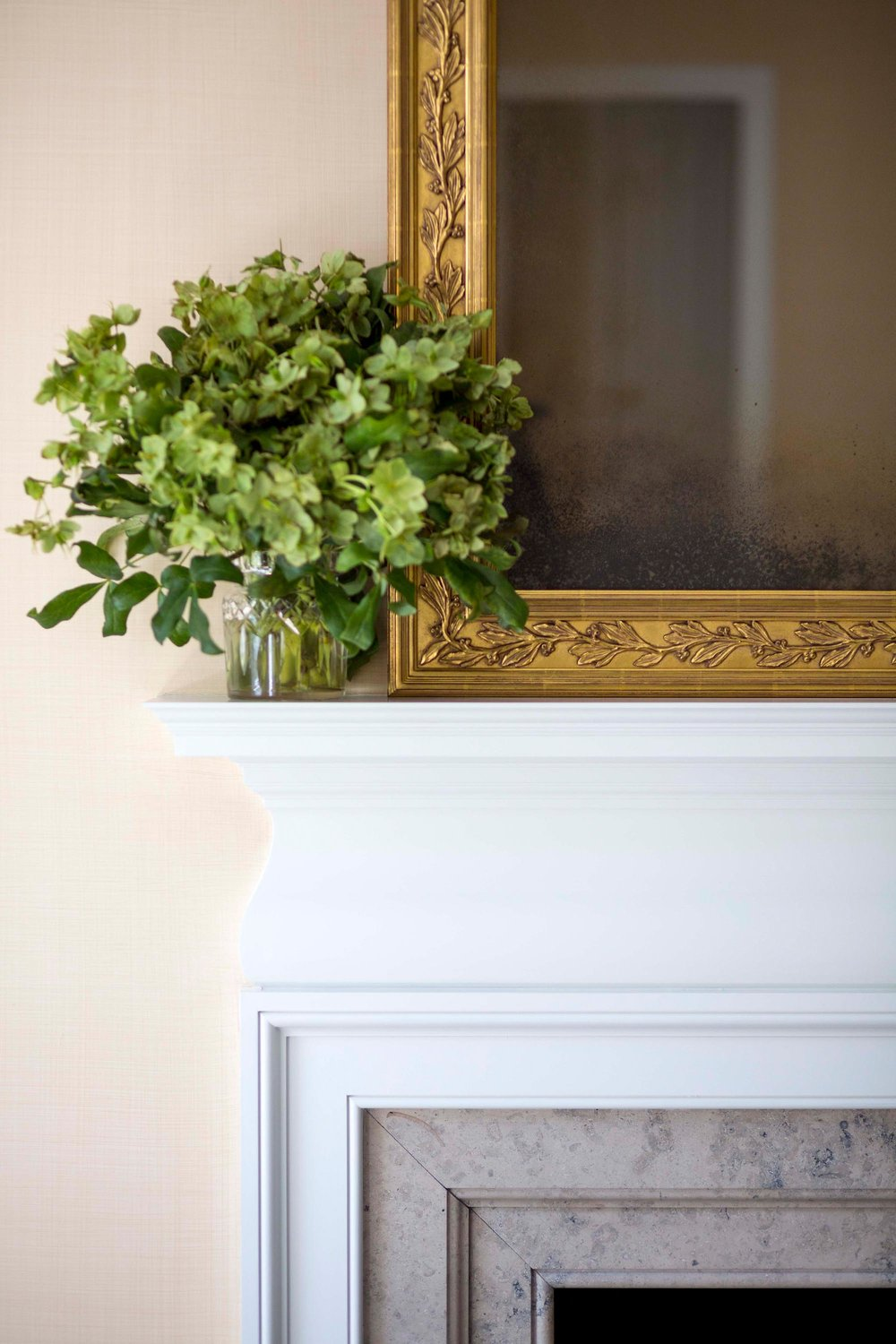 Gold framed mirror resting on white fireplace mantle
