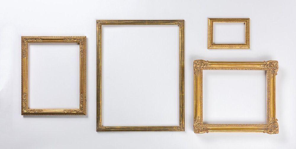 Four fancy picture frames laid out neatly