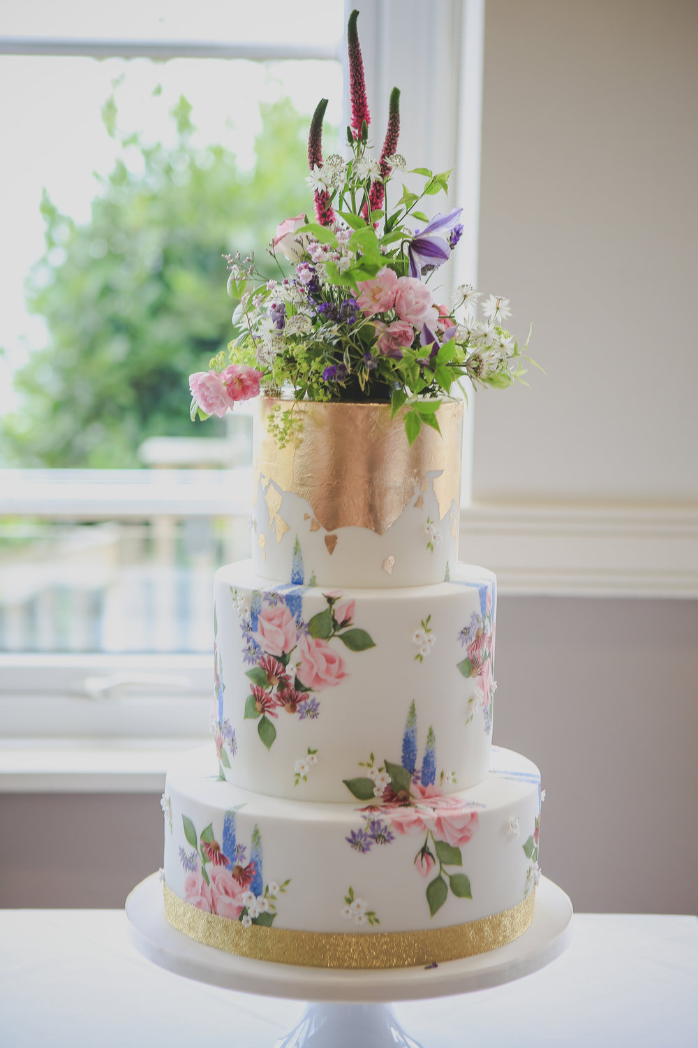 CORNISH WILDFLOWERS  This pretty 3 tier hand painted cake is decorated with Cornish wildflowers and finished with decadent gold leaf and a pretty posy of fresh blooms... perfect for a country garden wedding.