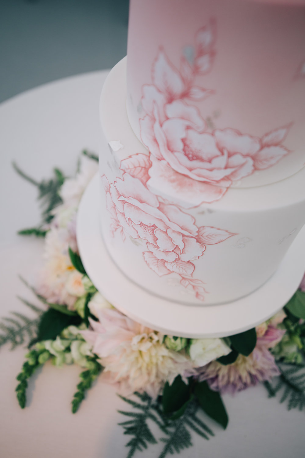 BLUSH OMBRE ROSES  An elegant 3 tier cake with a delicate blush ombre,hand painted with monochrome blooms in white and pink with touches of silver leaf.