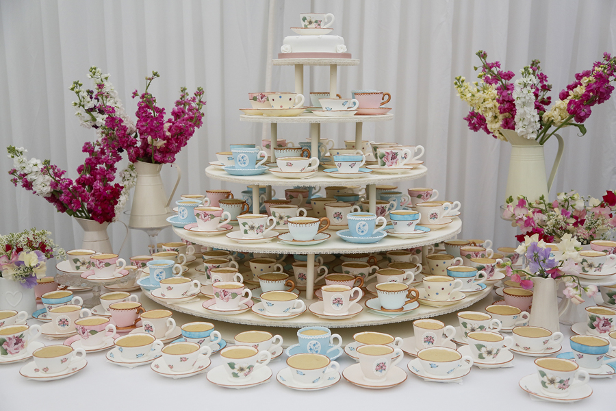 COMPLETELY EDIBLE TEACUP TOWER  A tower of 150 completely edible, hand painted teacups and saucers - one for each guest! The teacups and saucers are made from sugar and are filled with delicious sponge cake with a hidden jammy centre and topped with buttercream to look like tea. Each cup is individually hand painted with designs inspired by the couple. These Tea cup towers make a showstopping centrepiece in a venue and are a fantastic talking point for your guests. I can create as many or as few as you require!