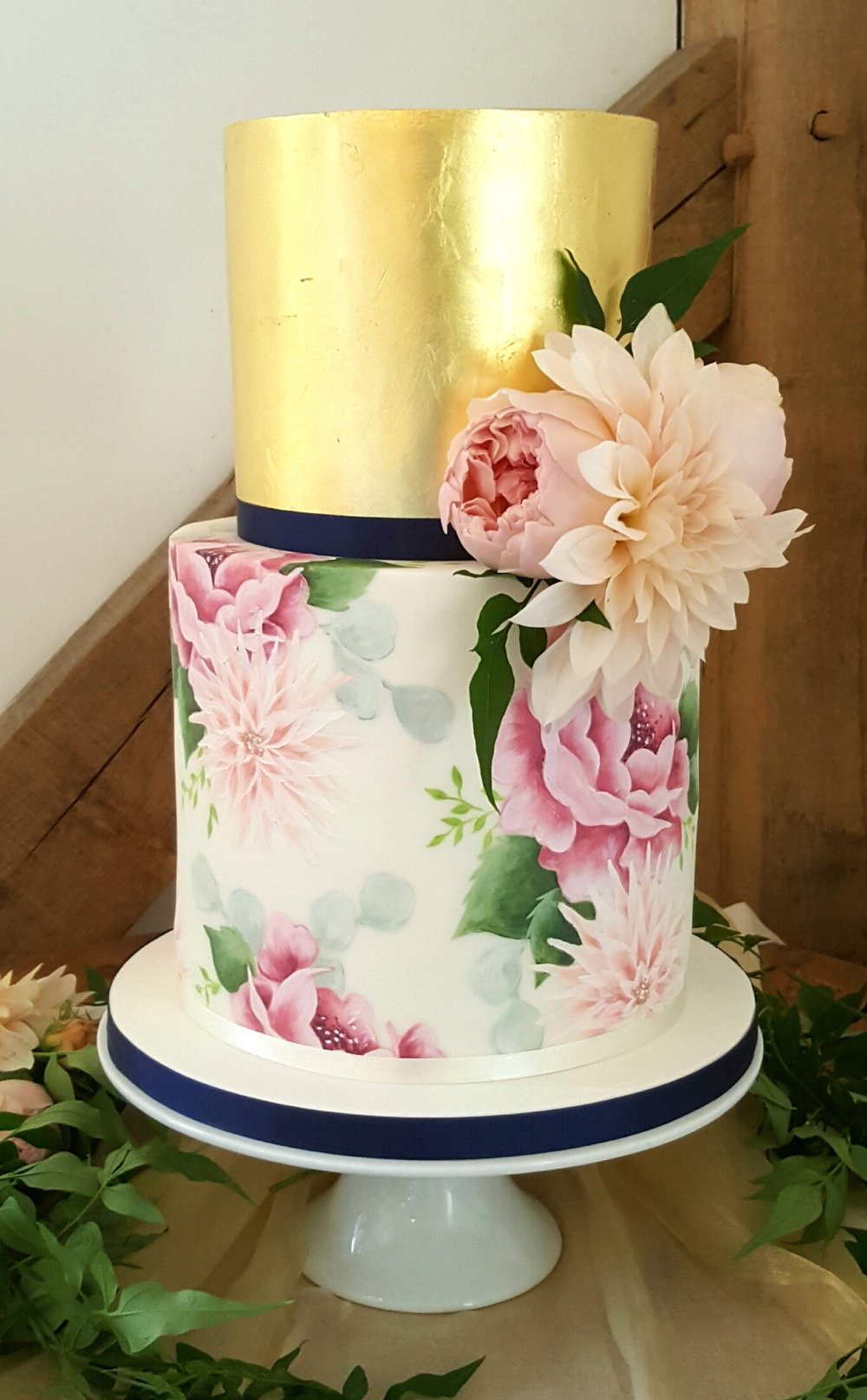 DELICATE FLORAL AND GOLD  A perfectly petite 2 tier wedding cake hand painted with an all over floral design featuring roses and dahlias. The top tier is completely covered in decadent, edible 24ct gold leaf and finished with fresh flowers to compliment the cake.