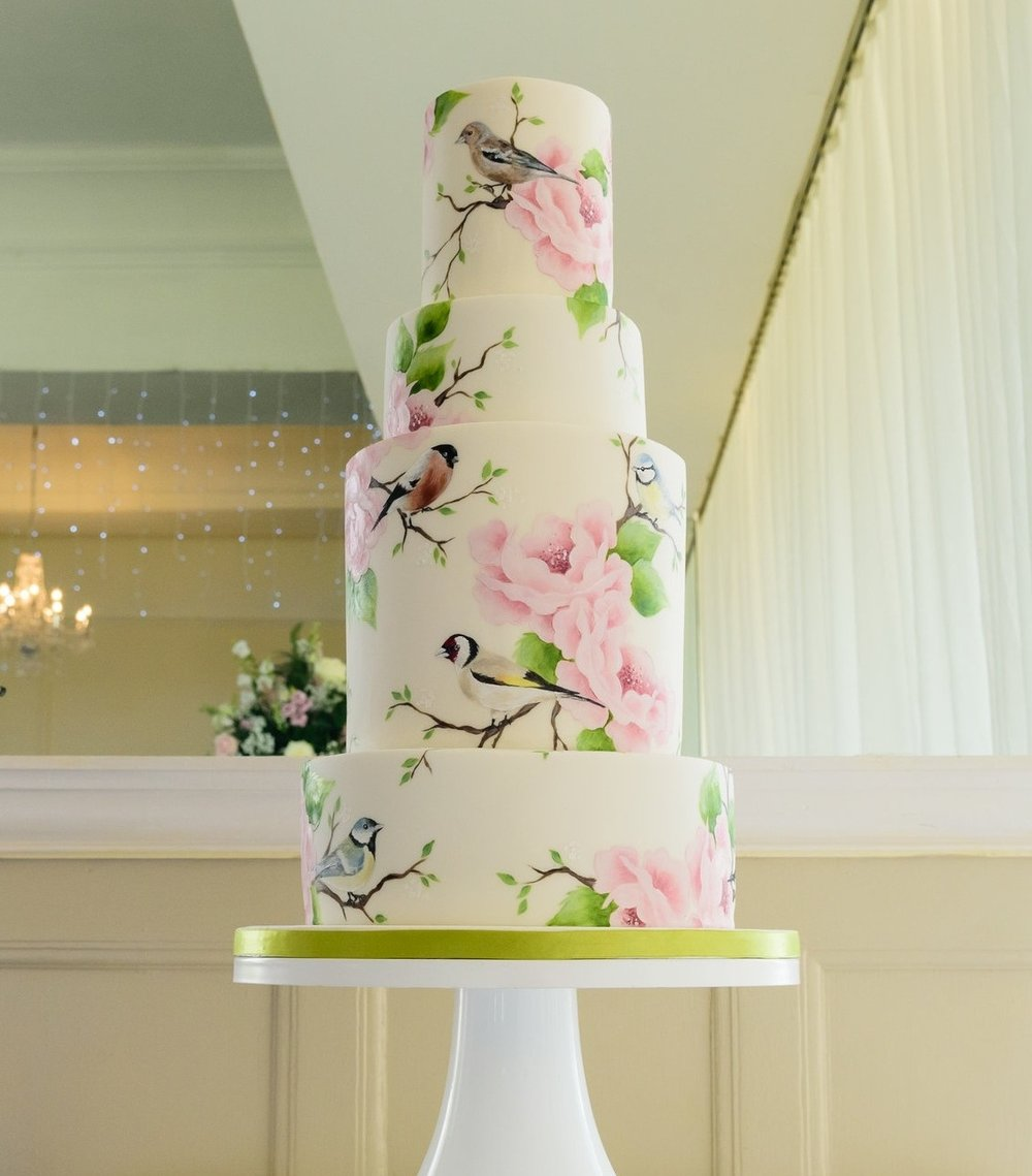 BRITISH GARDEN BIRDS  This showstopping 4 tier cake featured a selection of hand painted British garden birds alongside my signature blooms. The couple I designed it for were keen bird lovers and wanted this reflected in their cake. I loved the fact that they displayed their wedding cake in front of a mirror so guests could admire the design from all angles!