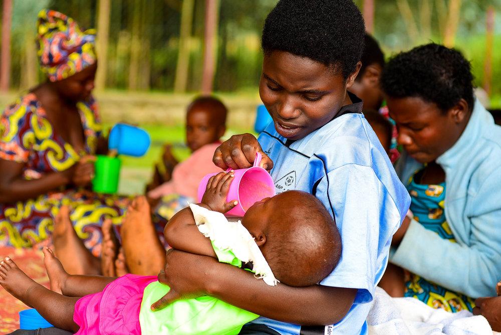 Umubyeyi agaburira umwana we Sosoma mu mahugurwa Umurima w'Ubuzima utanga ajyanye no kuboneza urubyaro   yabereye ku kigo nderabuzima cya Muzsanze mu karere ka Musanze, Rwanda.