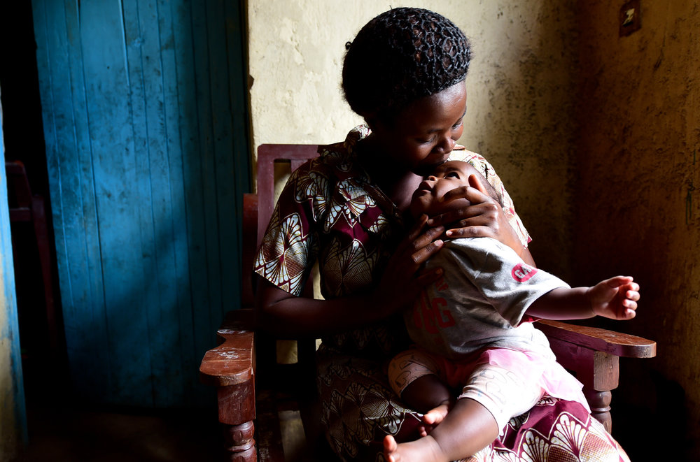 """Nyirantezimama Apollinarie, recent graduate of GHI's health center program in Musanze, and her daughter Nyauisaba Ada Toddey. """"She smiles and plays with other children now. This was not always happening before GHI,"""" Apollinarie said of Toddey."""