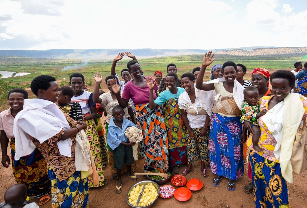 Burundian women enrolled in GHI's health and agriculture trainings at Mahama Refugee Camp wave to the camera during a cooking demonstration on October 6, 2017.