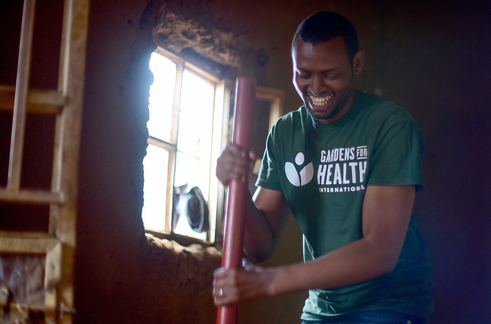 Solomon helps create an Earth Enable floor during GHI's October 2017 Umuganda Day.