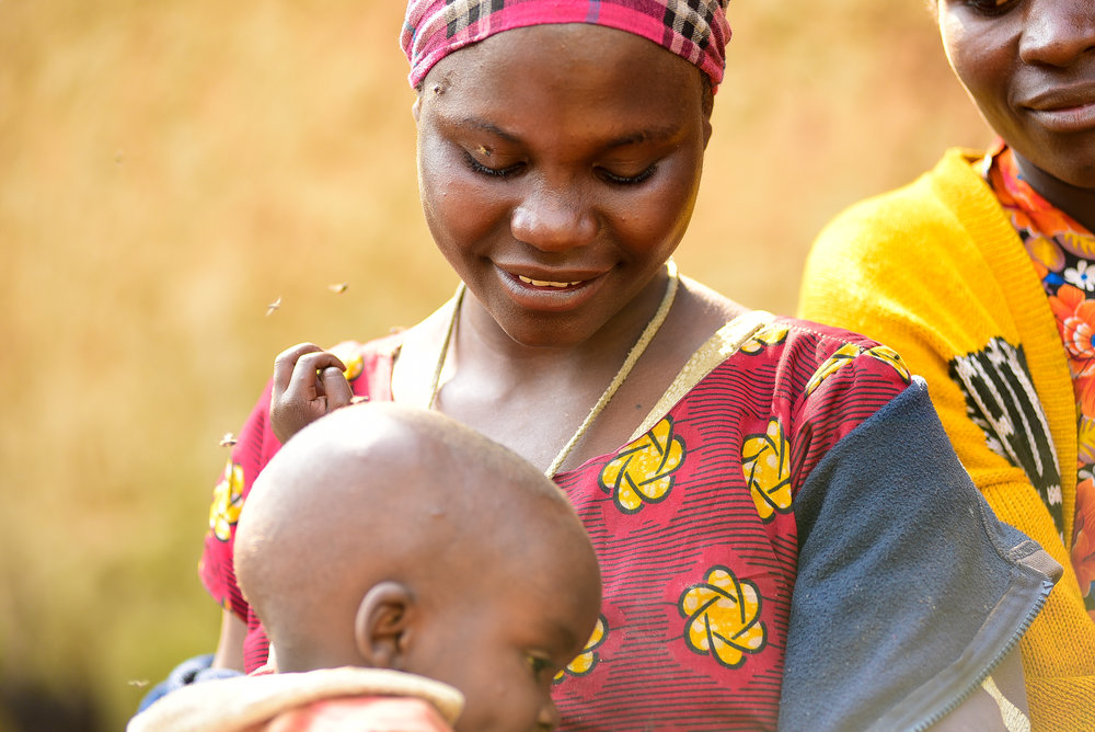 Claudine, a recent graduate of GHI, smiles at her son Itashako during last season's introductory agriculture training in Busogo, Musanze