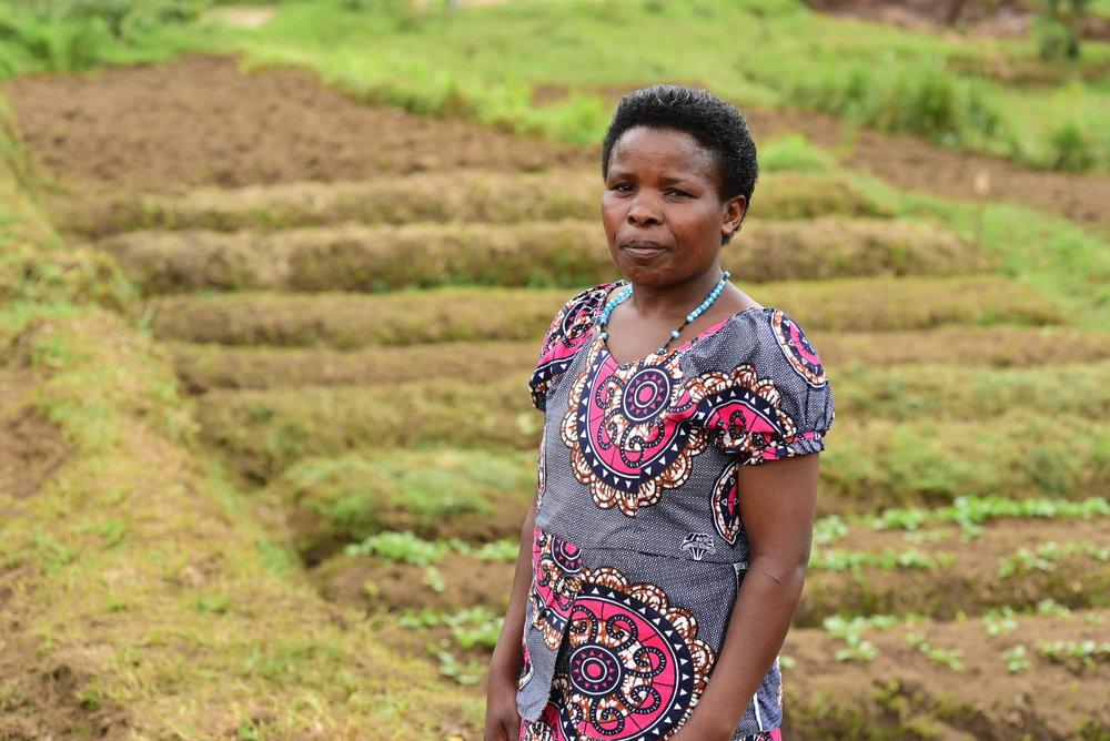 Nyirabukeyengenda Marguerithe in front of the EP Rutsiro garden in March 2018.