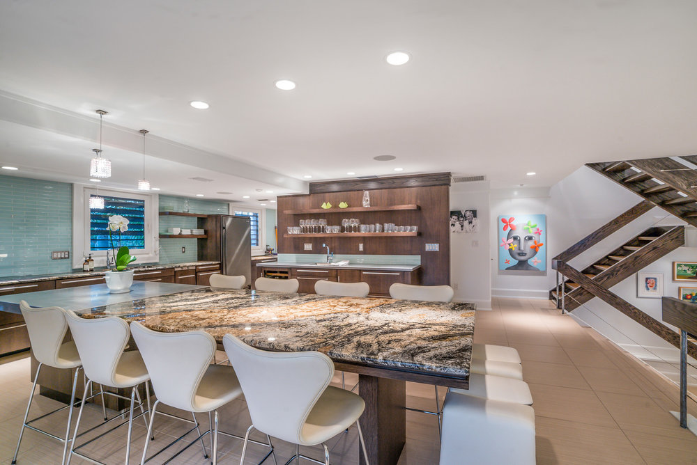 Another glance shows us the second half of the main living space, a chic kitchen and entertaining space, complete with wet bar, granite and stainless counters, and built-in dining space. Glass subway tiles and floating wood shelving make this mid-century-inspired kitchen au courant.
