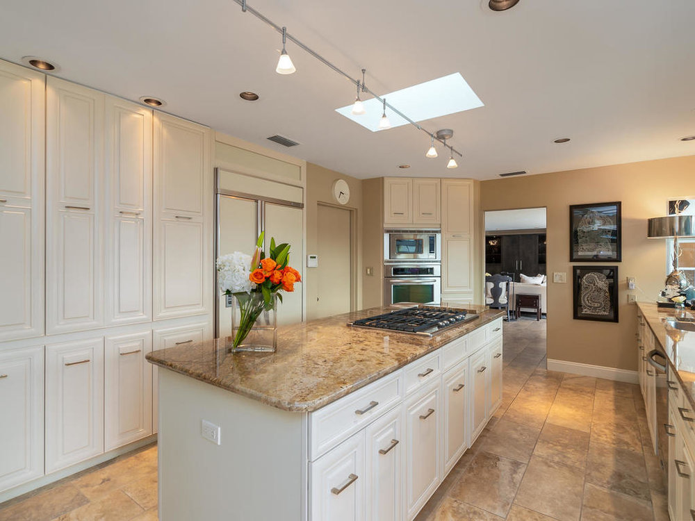 The light and bright kitchen features stainless appliances, 6-burner gas stove on cooking island, solid wood cabinetry, beautiful neutral granite, and sliding pull-out shelving in every cabinet (including under the sink! No more rummaging for cleaning supplies.)