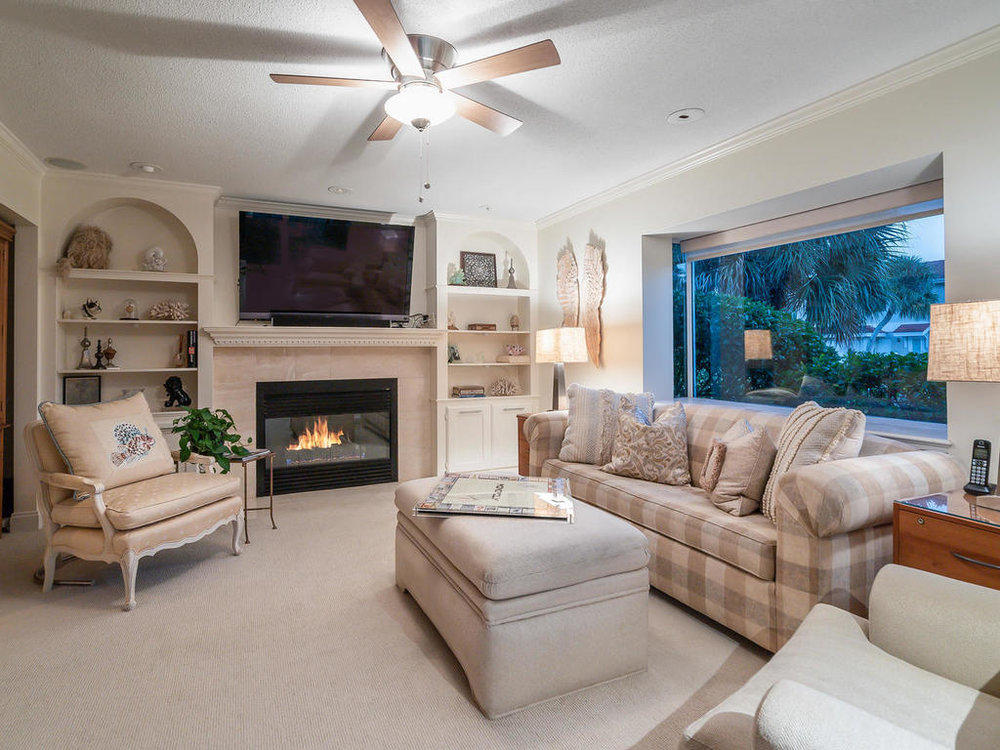 A third bedroom presently functions as a den, with built-in shelving, gas fireplace, and walk-out to pool.