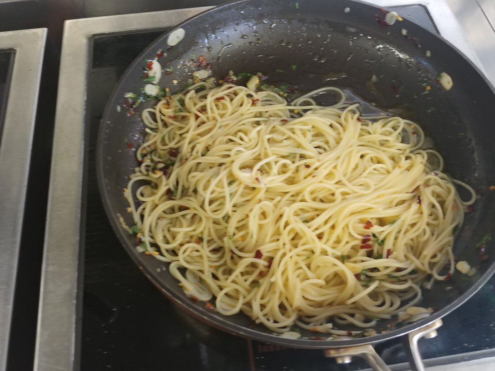 Don't drain - Instead, transfer it using tongs. Allow some of the starchy water with the pasta, in fact make sure you add some of the starchy water. The starchy water, the oil and the parmesan will make the sauce/coating for the pasta.