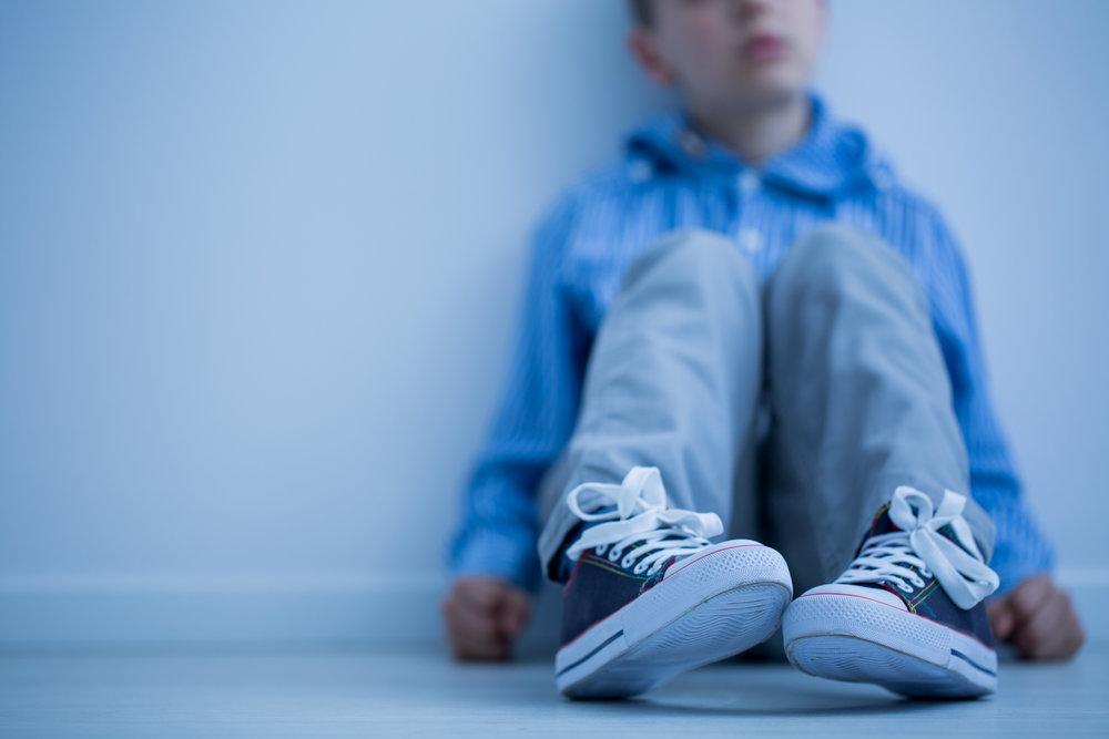 young boy sitting on the floor, sad.jpg