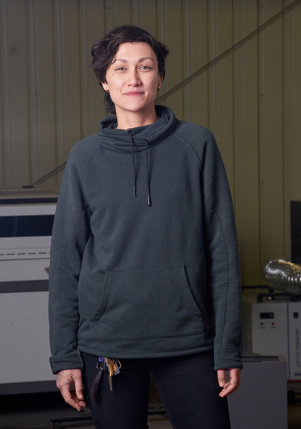 Natalie standing in front of laser cutting machine in Houston Texas