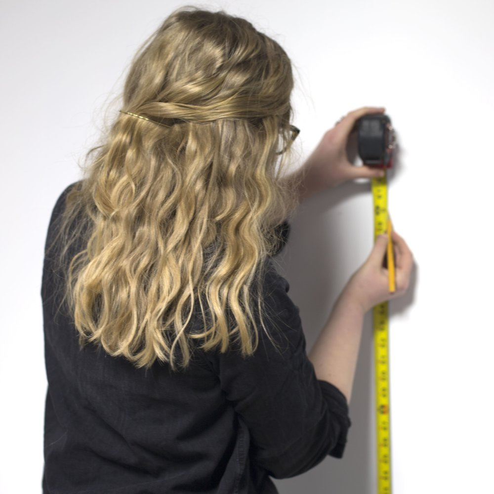 Person using tape measure and pencil to install laser cut signage
